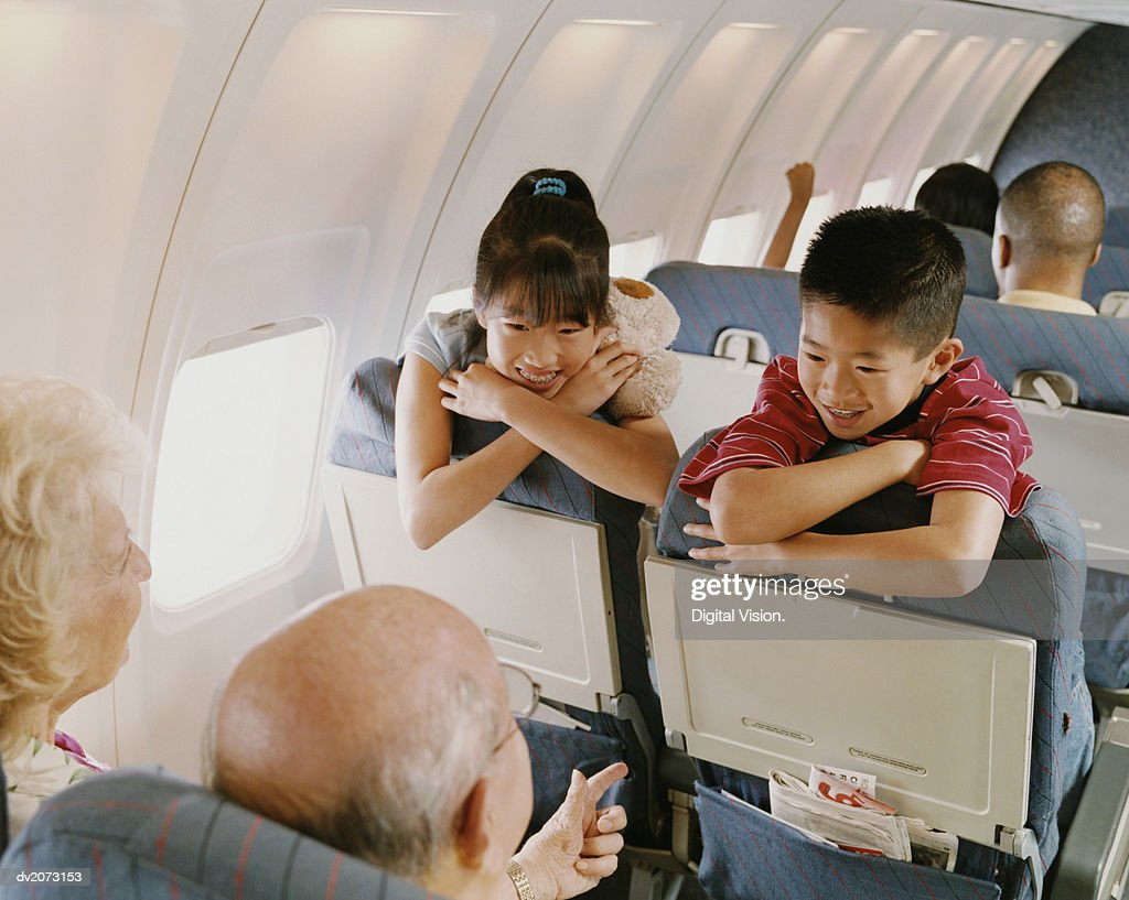 Young Boy and Girl Sit on a Plane, Talking to a Senior Couple Behind Them : Stock Photo