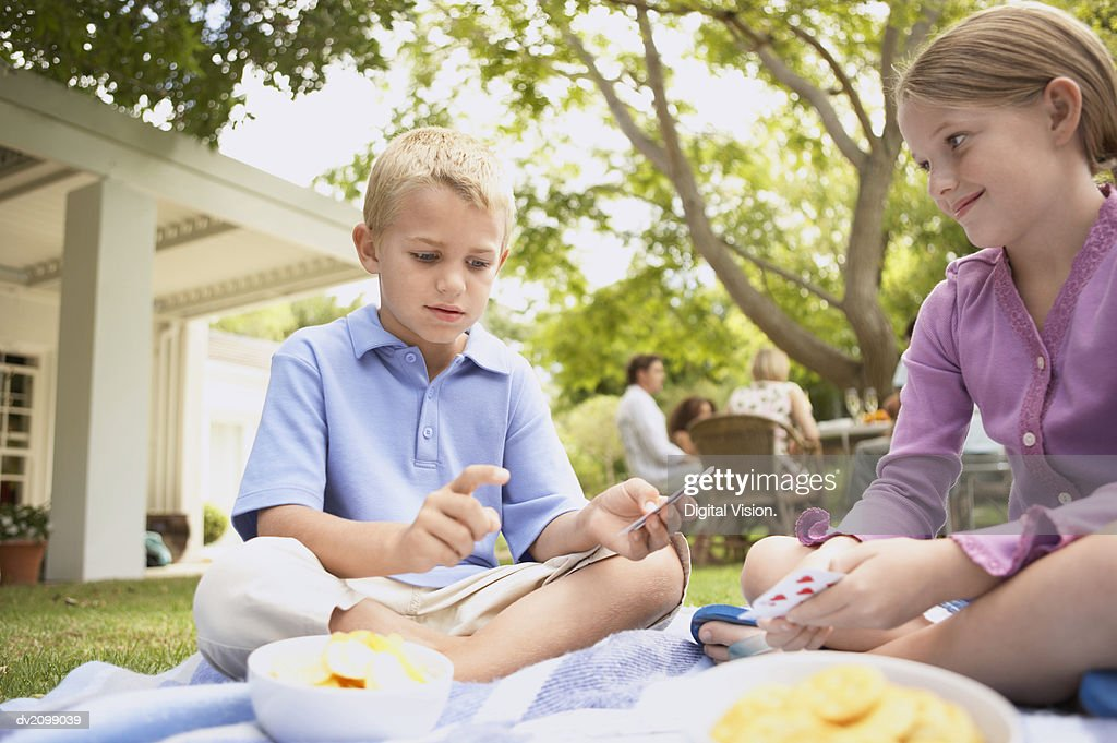 Young Boy and Girl Sit on a Rug in Their Garden, Playing a Card Game : Stock Photo