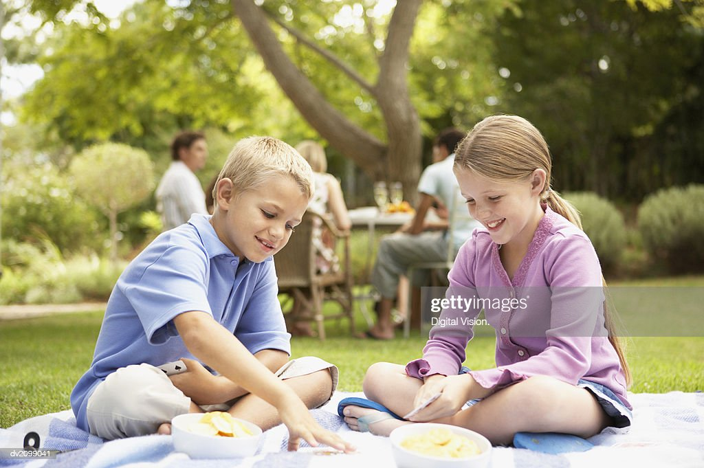 Young Boy and Girl Sit on a Rug in Their Garden Playing a Game of Cards : Stock Photo