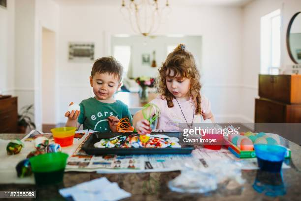 young boy and girl sitting at kitchen counter dying easter eggs - art and craft stock pictures, royalty-free photos & images