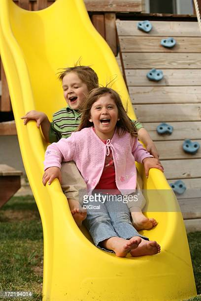 Young Boy And GIrl Sliding On The Slide Grining
