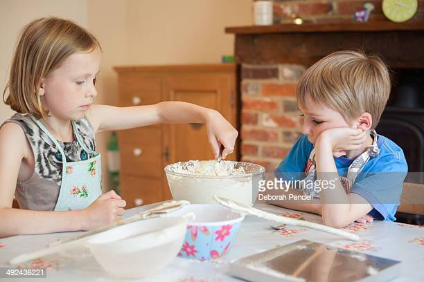 Young boy and girl stirring cake mixture