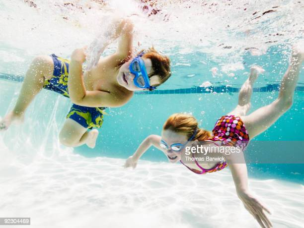 Young boy and girl swimming  underwater in pool