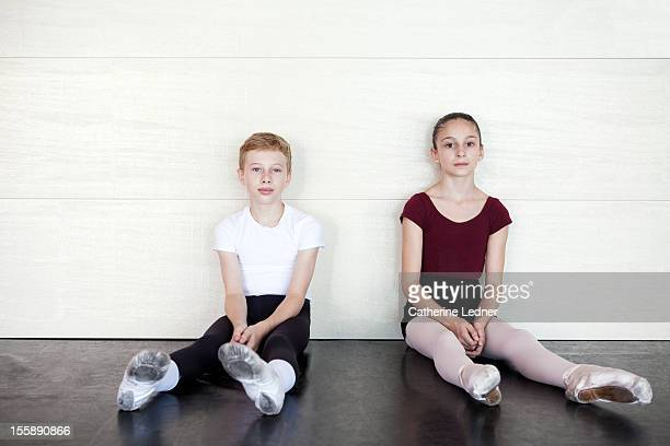 A young boy and girl taking a break from ballet