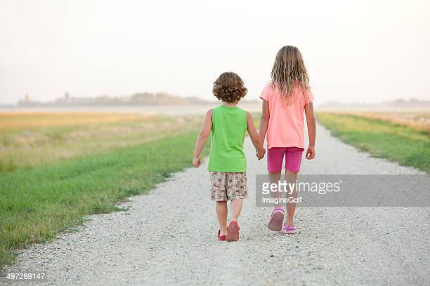 young boy and girl walking down gravel road - lane sisters stock photos and pictures