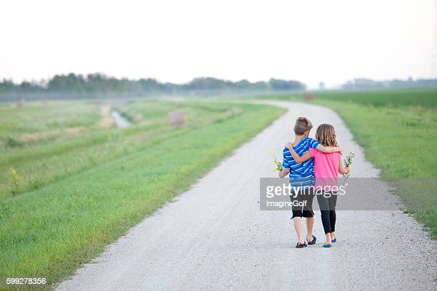 young boy and girl walking down gravel road - family with two children stock photos and pictures