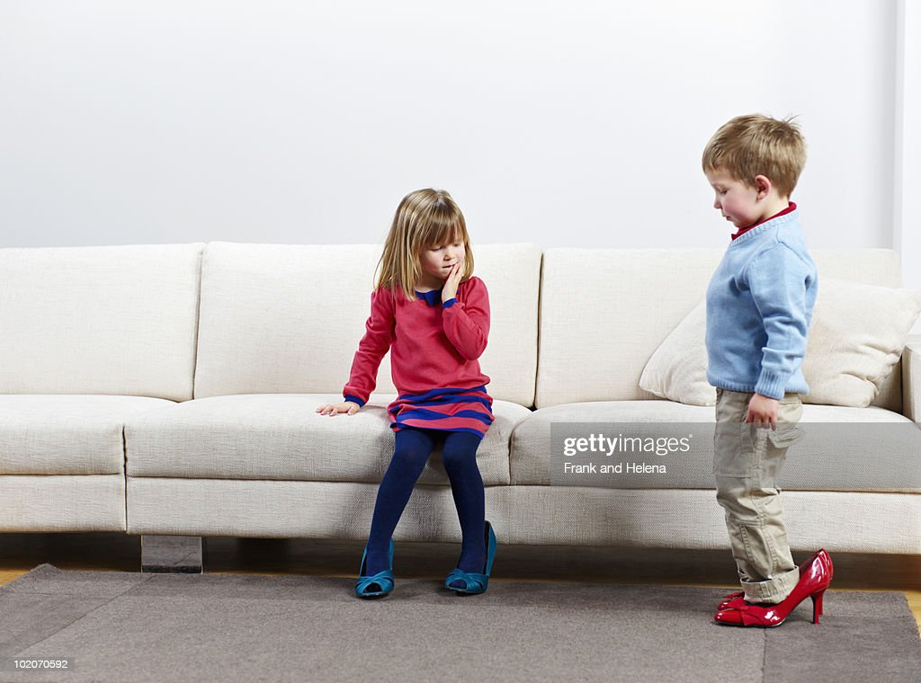Young boy and girl walking in high-heels : Stock Photo