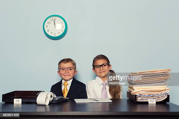 Young Boy and Girl Wearing Business Attire in Office