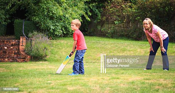 Young boy and grandparent play cricket