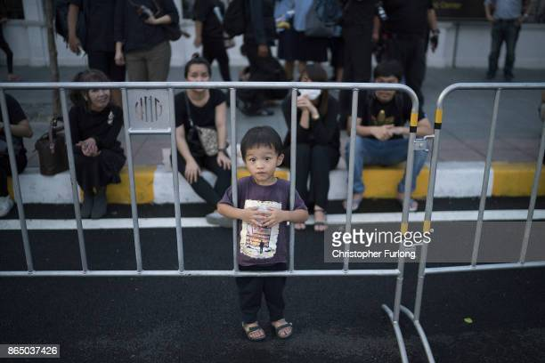 A young boy and his family gather to pay their respects to Thailand's late King Bhumibol Adulyadej as the city prepares for his cremation on October...