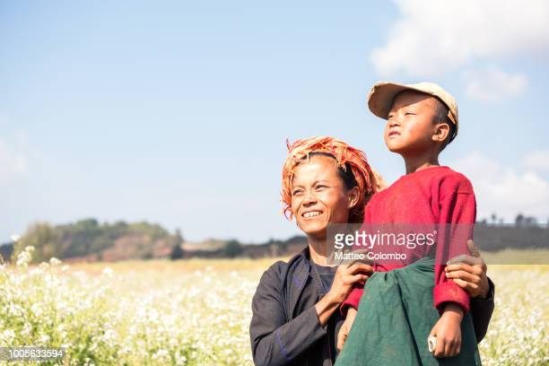 young boy and his mother in a field, myanmar - myanmar stock pictures, royalty-free photos & images