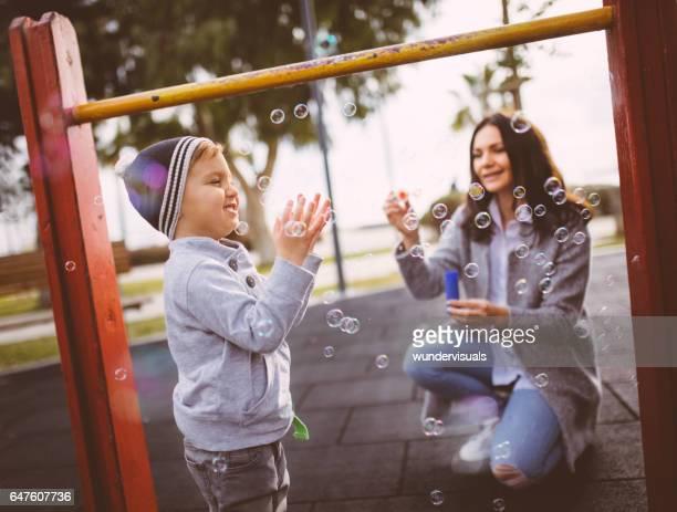 Jeune garçon et sa mère jouant avec des bulles au terrain de jeux