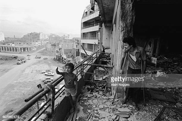 Young boy and his wounded father inspect the bombed out shell of their apartment in Beirut. The ruins testify to the intense fighting going on in the...