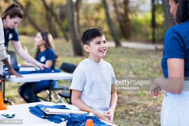 young boy and mature woman talk at park cleanup day - selfless stock pictures, royalty-free photos & images