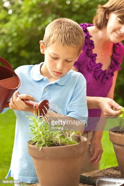 Young Boy and Mother Home Gardening, Planting flowers in pot