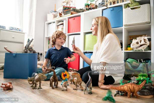 young boy and mother playing with toys together at home - dinosaur stock pictures, royalty-free photos & images