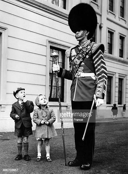 Young boy and sister looking at Horse Guard Drum Major during full dress rehearsal at Wellington Barracks, on September 20, 1955 in London, United...