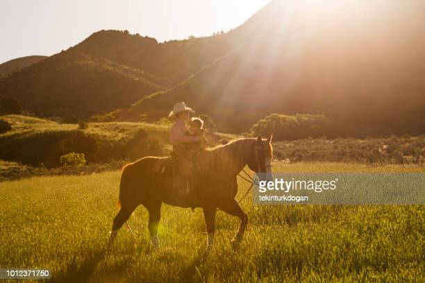 young boy and sister riding horse at countryside of santaquin valley of salt lake city slc utah usa - spanish fork utah stock pictures, royalty-free photos & images