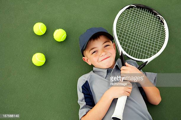 Young Boy and Tennis Player Lying Down on Tennis Court