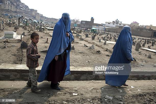 A young boy and two afghan women wearing burqas walk past a cemetery in a western Kabul Afghanistan neighborhood March 2 2009 Kabul has an estimated...