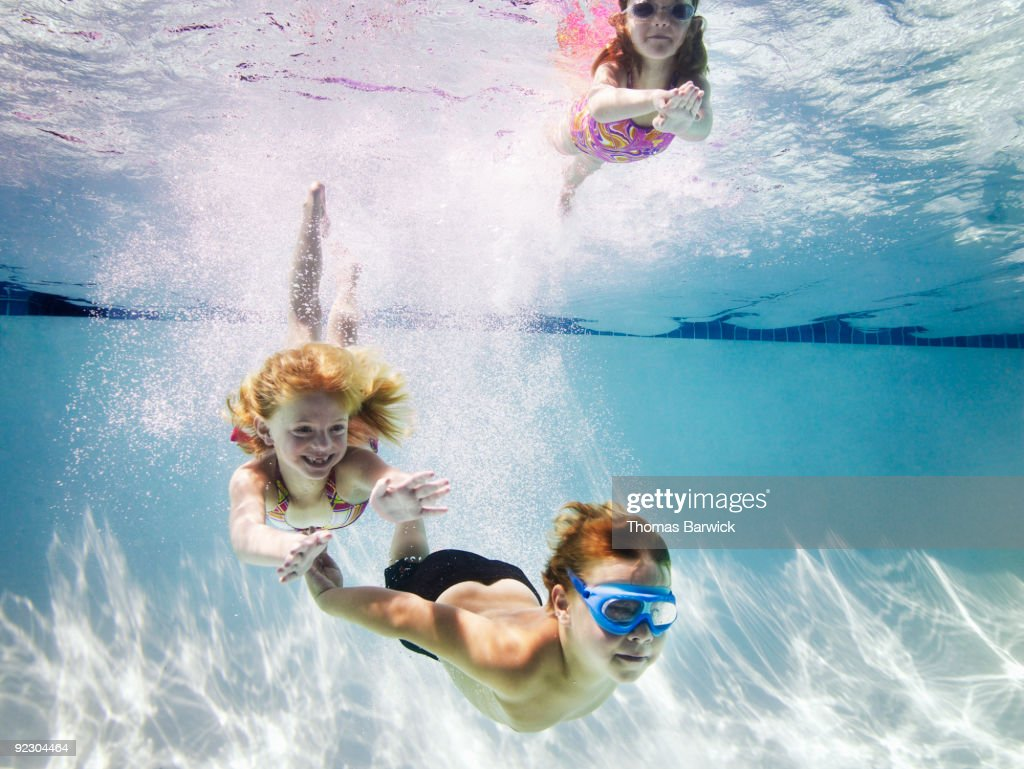 Young boy and two young girls underwater : Stock Photo