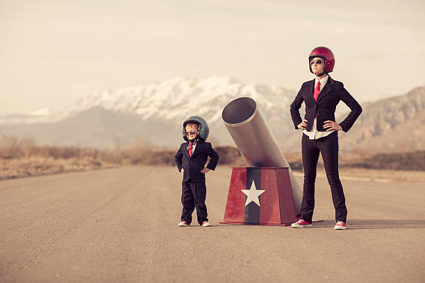 Young Boy And Woman Business Team With Human Cannon Wall Art