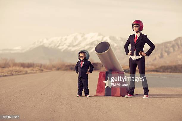 Young Boy and Woman Business Team with Human Cannon