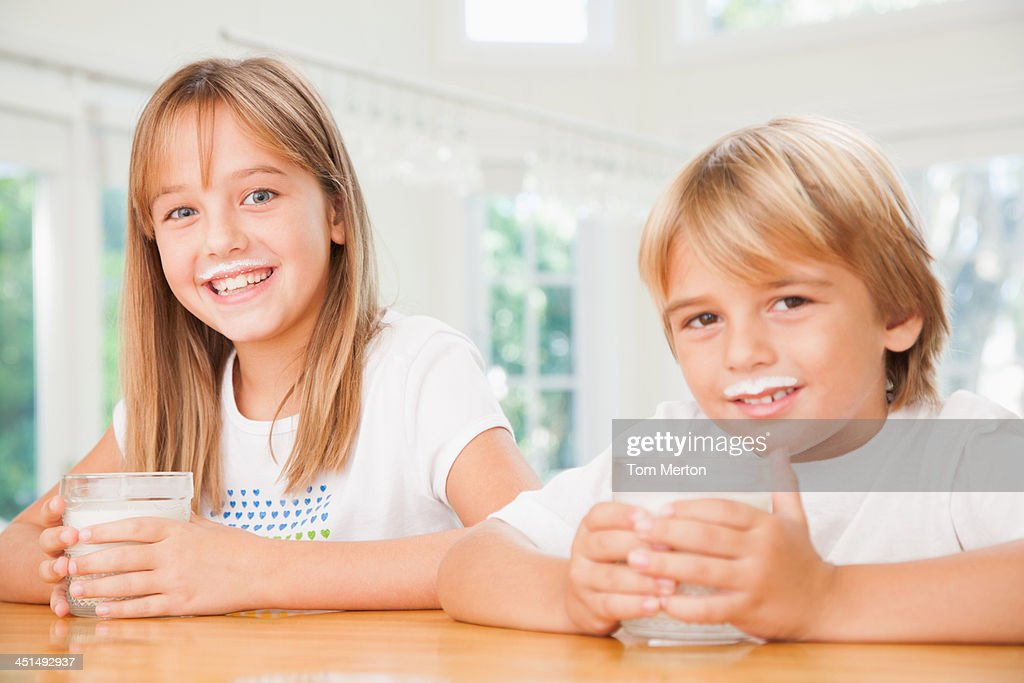 Young boy and young girl in kitchen with glasses of milk : Stock Photo