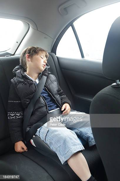Young boy asleep in back of car