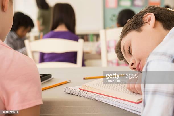 Young boy asleep in classroom
