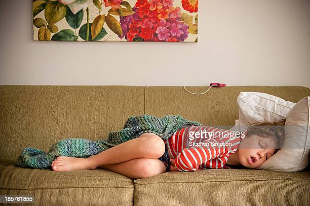 young boy asleep on living room couch
