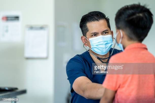 young boy at a doctors appointment wearing a mask. - fatcamera stock pictures, royalty-free photos & images