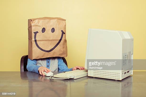 Young Boy at Computer with Paper Bag Smiley Face