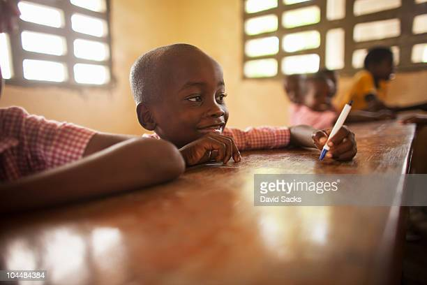 young boy at desk in school - education stock pictures, royalty-free photos & images