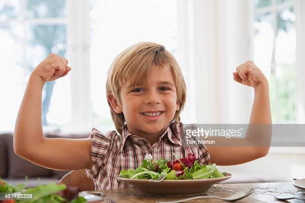 Young boy のダイニングルームテーブルの屈曲