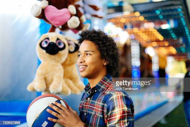 Young boy at funfair, playing on fairground stall, holding basketball