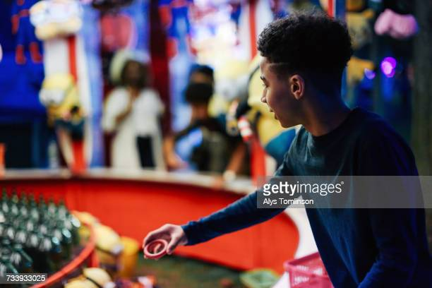 Young boy at funfair, playing on fairground stall