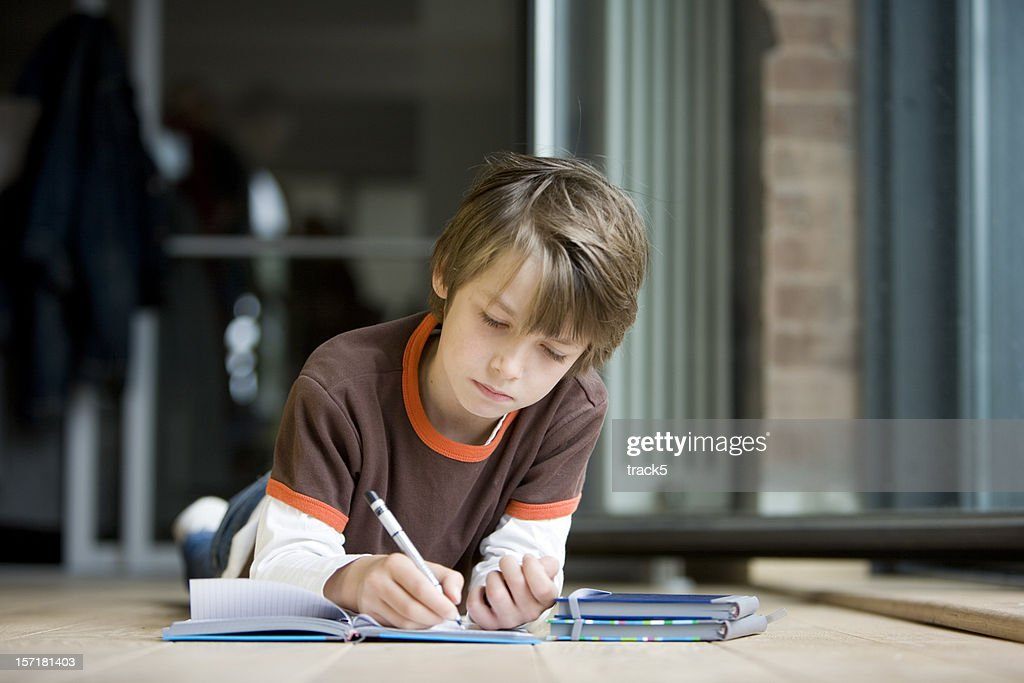 Young Boy At Home Concentrating Hard On His Homework Stock Photo