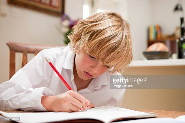 Young boy at home writing in school text book at the dining table