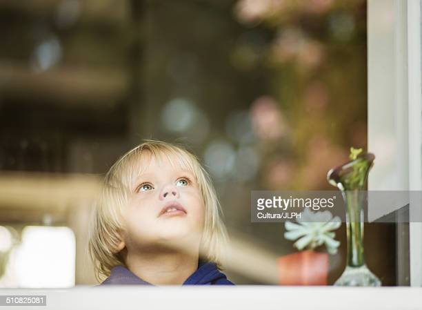 Young boy at house window gazing upward
