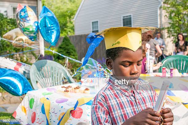 Young boy at kindergarten graduation, wearing paper mortar board, holding certificate