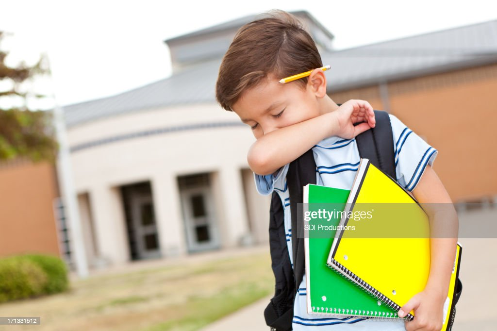Young boy at school coughing into his arm : Stock Photo