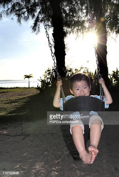 young boy at swing - 北マリアナ諸島 ストックフォトと画像