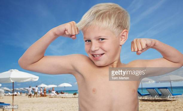 Young boy at the beach flexing biceps