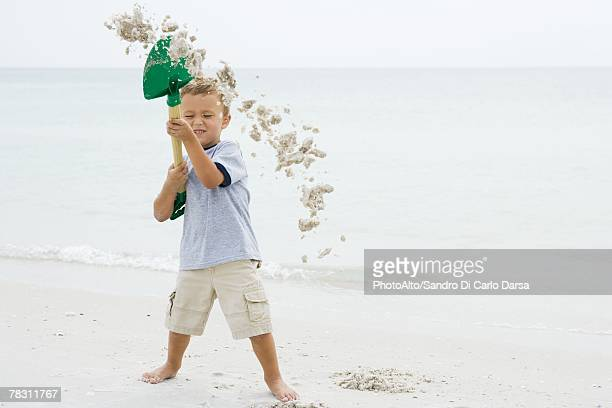 Young boy at the beach holding up shovel, throwing sand, eyes closed