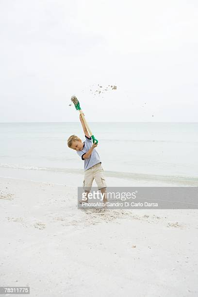 Young boy at the beach holding up shovel, throwing sand