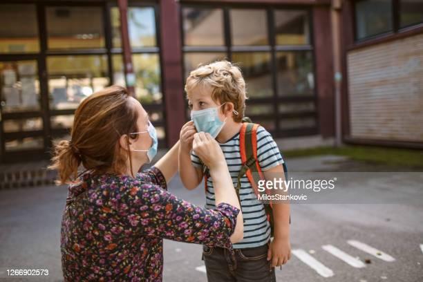 giovane ragazzo di nuovo a scuola in tempo pandemico - arrivo foto e immagini stock
