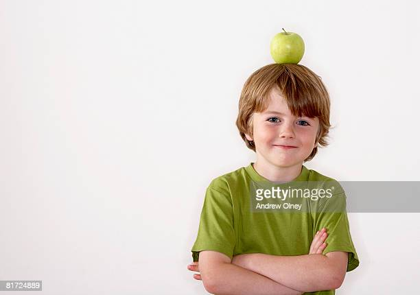 Young boy balancing apple on his head
