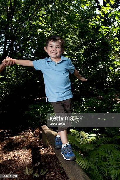 Young boy balancing on a fence