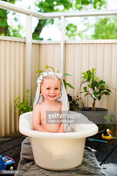A young boy bathing in a tub